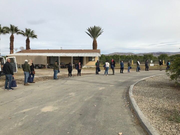 A line of appropriately distanced farmworkers outside at Tudor Ranch to get vaccinated for COVID-19.