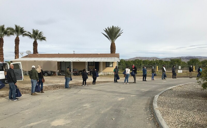 A line of socially distanced farmworkers outside at Tudor Ranch in Mecca.