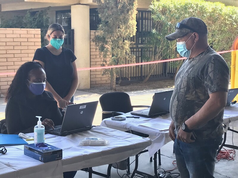Masked farmworker stands before the registration table manned by two nurses at Anthony Vineyards.