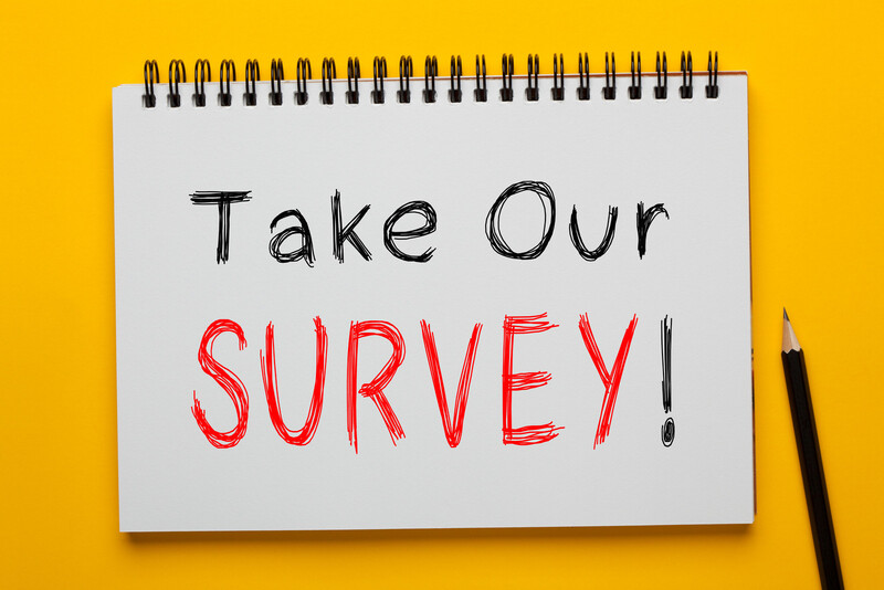"""Take Our Survey"" is printed in black and red letters on a white tablet with a pencil nearby and a  bright yellow background."