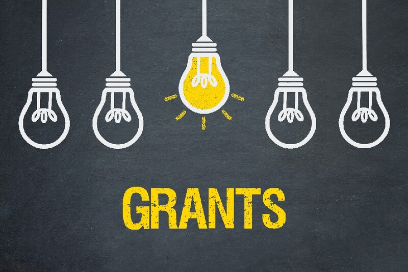 "Five lightbulbs hanging from the ceiling; the background is dark gray with ""Grants"" in bright yellow. The middle bulb is on."